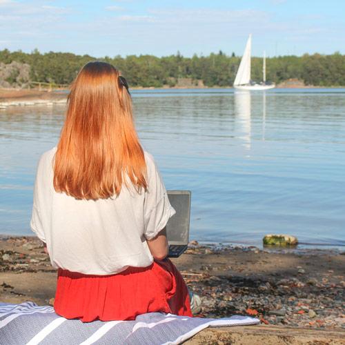 Nainen istuu rannalla ja käyttää läppäriä.