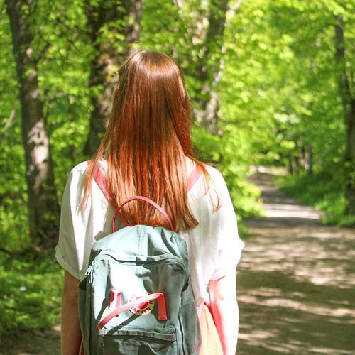 Nainen kävelee aurinkoisessa metsässä polkua pitkin.
