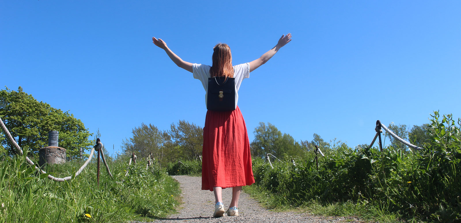 Nainen kävelee hiekkapolkua pitkin kädet ylhäällä.